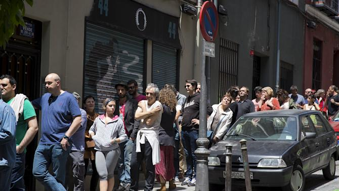Voters queue outside a poling station during regional and municipal elections outside Madrid
