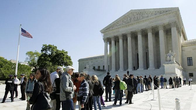 """Members of the public line up outside the Supreme Court in Washington, Wednesday, April 25, 2012, as the court held a hearing on Arizona's """"show me your papers"""" immigration law . (AP Photo/Charles Dharapak)"""