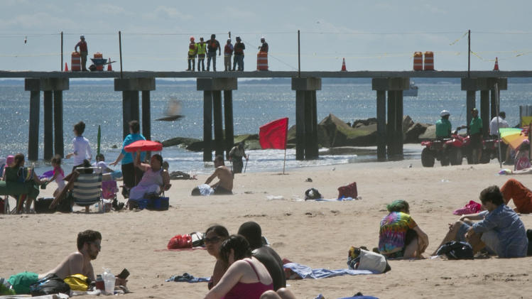 This June 12, 2013 photo shows sunbathers at the beach as workers continue repairs to a pier that was damaged during superstorm Sandy in the Coney Island neighborhood of the Brooklyn borough of New York. (AP Photo/Bebeto Matthews)
