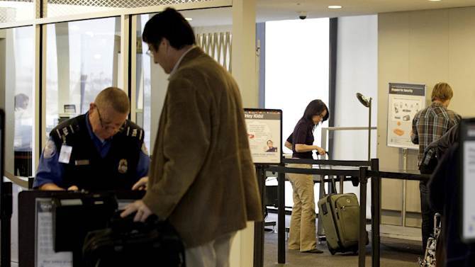 FILE - In this Nov. 17, 2011 photo, travelers move through the security area of Newark Liberty International Airport in Newark, N.J.  After a man was arrested at Los Angeles International Airport wearing a bulletproof vest, flame-resistant pants and had a suitcase full of weapons, the TSA has restated what air travelers are allowed to bring along. (AP Photo/Julio Cortez, File)