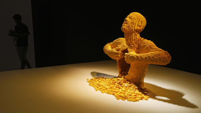"""Visitor walks past """"Yellow"""" during the media preview of The Art of the Brick exhibition in Singapore"""