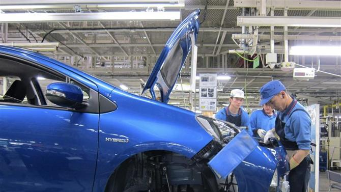 File photo of an assembly line worker attaching the bumper onto the body of a Toyota Aqua at a factory of the automaker's subsidiary, Kanto Auto Works, in Kanegasaki
