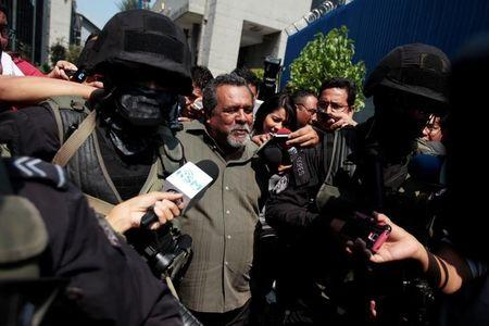 Gang truce mediator Raul Mijango is secured by policemen in a court of justice after his arrest on allegations of bringing banned objects into prisons and being an associate of gang members in San Salvador