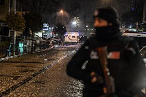 A Turkish police officer stands guard along a street…