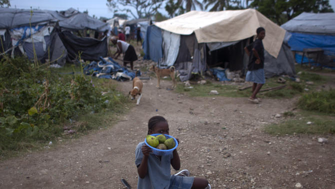 A girl sits on the ground as she sells avocado at a camp for people displaced by the 2010 earthquake after the passing of Tropical Storm Isaac in Port-au-Prince, Haiti, Monday Aug. 27, 2012. (AP Photo/Dieu Nalio Chery)