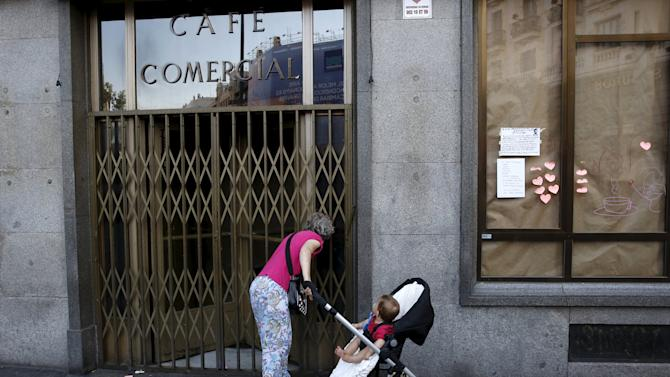 A woman looks through the door of El Comercial cafe in Madrid