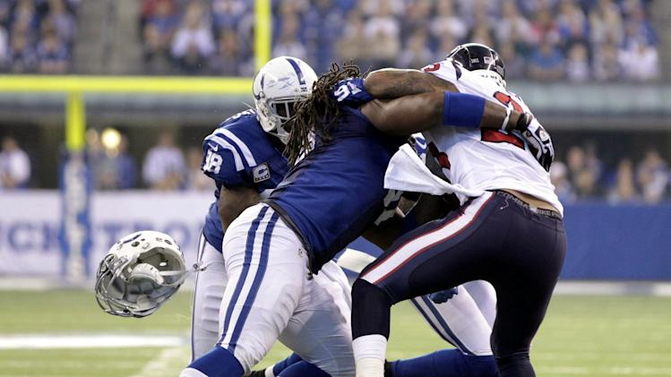 Indianapolis Colts' Ricardo Mathews (91) looses his helmet as he tackles Houston Texans' Arian Foster (23) during the first half of an NFL football game, Sunday, Dec. 30, 2012, in Indianapolis. (AP Photo/AJ Mast)