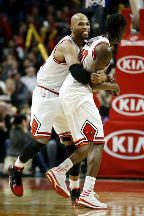 Chicago Bulls forward Taj Gibson, left, celebrates with Tony Snell, right, after Snell scored a 3-pointer during the second half of an NBA basketball game on Saturday, Dec. 21, 2013, in Chicago
