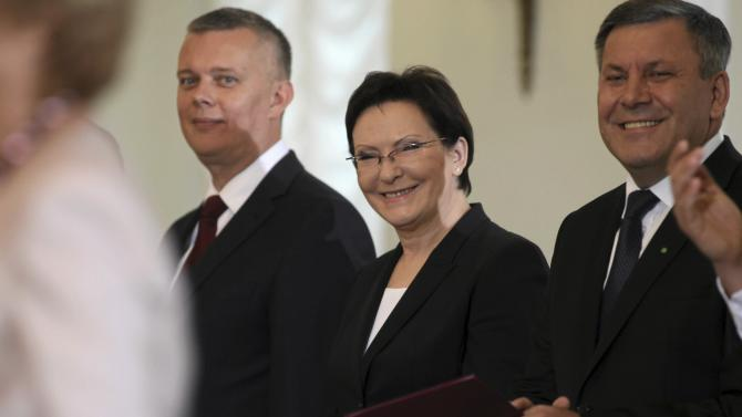 Newly sworn in Prime Minister Kopacz smiles with Deputy Prime Minister Piechocinski and Defense Minister Siemoniak as they attend a swearing-in ceremony of the new cabinet at the Presidential Palace in Warsaw