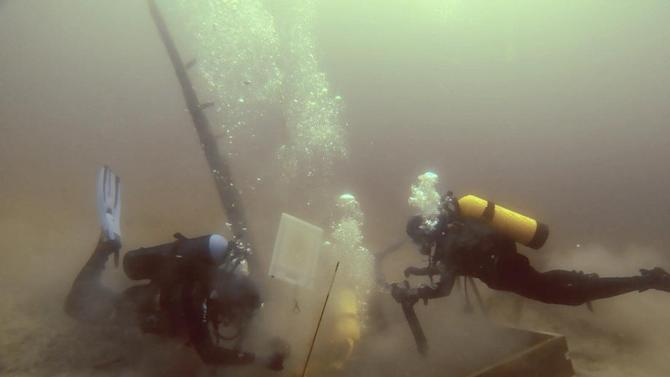 In this photo taken June 16, 2013, divers inspect a hole being dug beside a wooden beam jutting from the floor of Lake Michigan that an exploration group believes may have been part of the 17th century ship the Griffin. (AP Photo/Great Lakes Exploration Group, David J. Ruck)