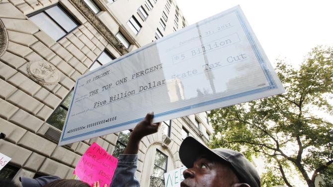 Member of the Occupy Wall St movement holds a sign aloft while protesting on 5th Avenue in front of Murdoch's house during a march through the upper east side of New York