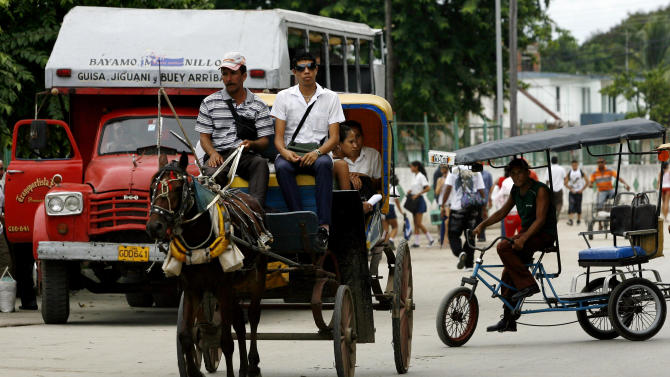 People use a horse drawn carriage as public transport as a public bus is seen behind in Bayamo, Cuba, Friday Oct. 22, 2010. The Cuban government laid out details of the taxes that Cubans will face as they go to work for themselves for the first time after announcing last month that it will lay off half a million state workers, nearly 10 percent of the island's work force. (AP Photo/Ismael Francisco, Prensa Latina)