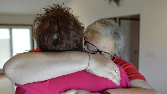 April Miller, right, and her partner Karen Roberts embrace after reading the decision of the United States Sixth Circuit Court of Appeals refusing to hear Rowan County Clerk Kim Davis' appeal ordering her to issue marriage licenses because of her religious beliefs in Morehead, Ky., Wednesday, Aug. 26, 2015. (AP Photo/Timothy D. Easley)