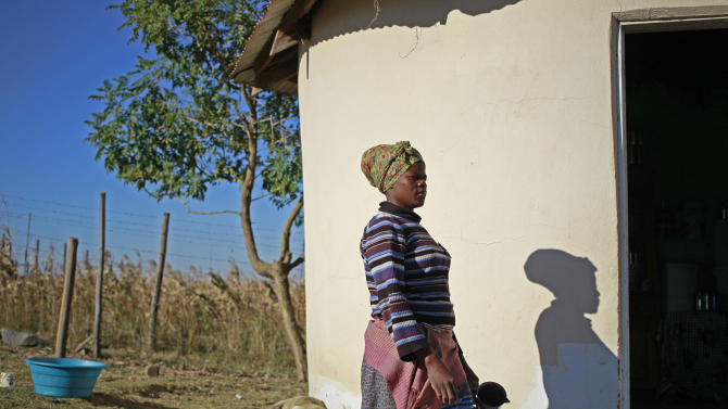 A woman walk towards her doorway, near the house and birth place of former South African President Nelson Mandela in Qunu, South Africa, Wednesday,  June 12, 2013. Former South African President Nelson Mandela remains in the hospital for a fifth day. The 94-year-old icon was hospitalized on Saturday for a recurring lung infection. (AP Photo/Schalk van Zuydam)