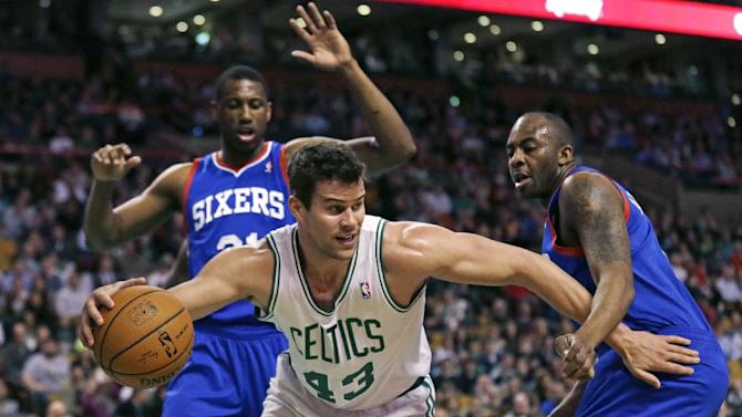 Boston Celtics center Kris Humphries (43) tries to break free from Philadelphia 76ers guard James Anderson, right, and forward Thaddeus Young, left, after grabbing a rebound during the first quarter of an NBA basketball game Friday, April 4, 2014, in Boston
