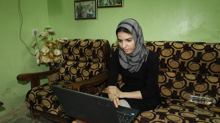 In this Sept. 27, 2012 photo, college student Shahad Abdul-Amir Abbas, 21, studies at her home in Baghdad. She lost her father in sectarian killings in 2005 and now volunteers to help orphans at her mother's orphanage in addition to attending the University of Medicine. (AP Photo/Karim Kadim)