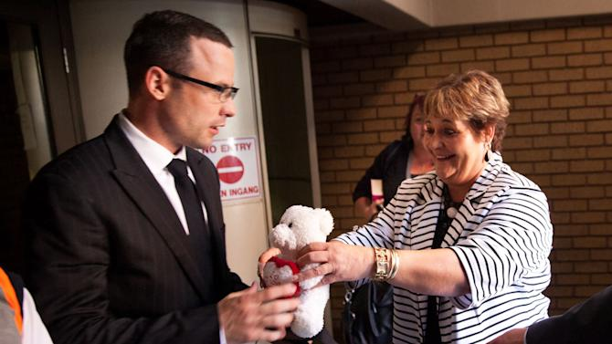A supporter hands Oscar Pistorius a teddy bear in court during his ongoing murder trial in Pretoria, South Africa, Tuesday, May 13, 2014. Pistorius is charged with the shooting death of his girlfriend Reeva Steenkamp on Valentine's Day in 2013. (AP Photo/Daniel Born, Pool)