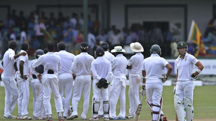 South African batsman Faf du Plessis, right, watches as his teammate Hashim Amla, second right, and Sri Lankan cricket team members wait for third umpire's decision against him during the fifth day of the second test cricket match between South Africa and Sri Lanka in Colombo, Sri Lanka, Monday, July 28, 2014. (AP Photo/Sanka Gayashan)