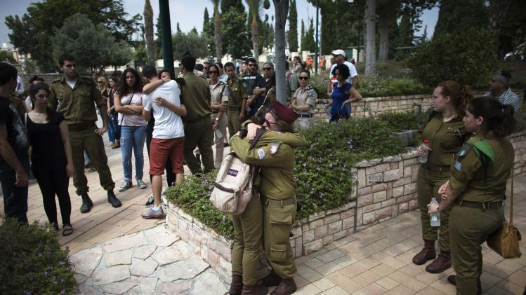 Friends, relatives and comrades of Israeli soldier Yifrah mourn during his funeral near Tel Aviv