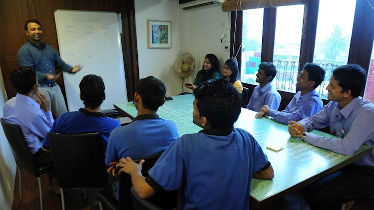 The founder of India's door to door pick-up and delivery service 'Get My Peon', Bharat Ahirwar (L), talks to his staff at their office in Mumbai on July 11, 2014