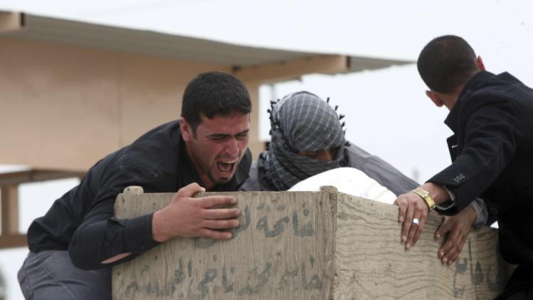 Mourners cry as they hold onto the coffin of a relative who was killed in an attack in Hilla, during a funeral in Naja
