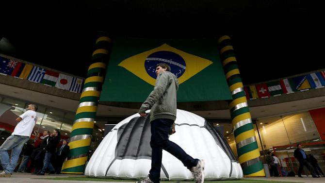 In this Tuesday, June 10, 2014 photo, a man walks near a shopping center where a large Brazil flag and half of a soccer ball decorate the entrance in Sao Paulo, Brazil. Soccer fans will focus on Brazil and the start of the World Cup on Thursday, but investors have been pumped up about that nation's stock market for months. (AP Photo/Julio Cortez)