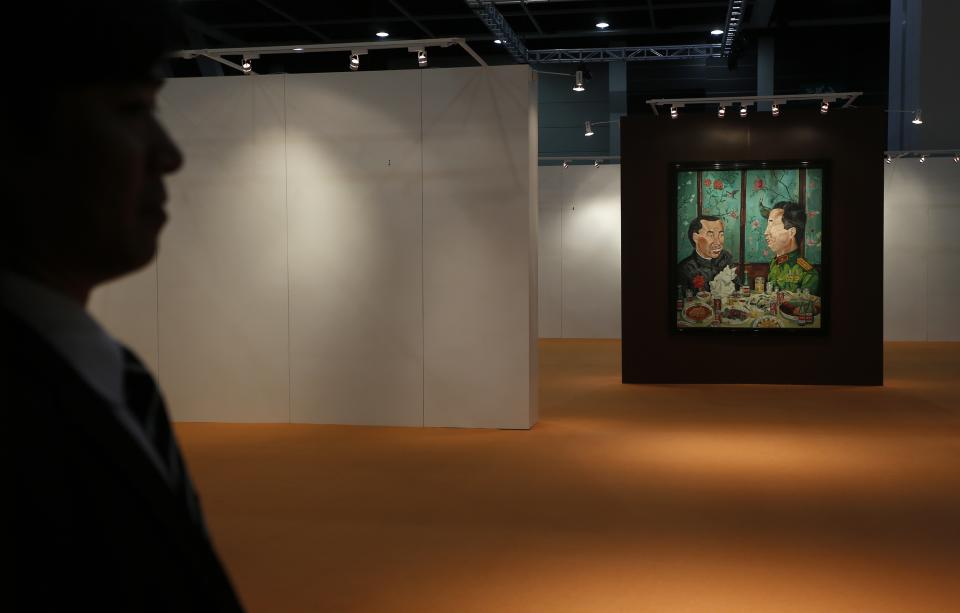 "A security guard stands next to a painting "" Revolutionary Family Series – Invitation to Dinner "" by Chinese artist Liu Wei at the Sotheby's autumn auction in Hong Kong Monday, Oct. 8, 2012. The work sold for US$2.24 million, set a world auction record for the artist. (AP Photo/Vincent Yu)"