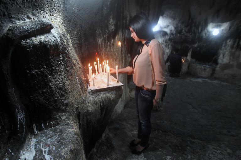 An Iraqi Christian lights a candle at the Mother of Continuous Aid Church in the ​​Christian village of Ankawa, on September 22, 3013