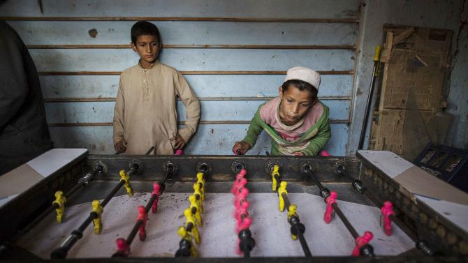 A boy plays foosball at a slum on the outskirts of Islamabad