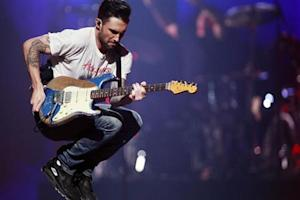 Maroon 5 lead singer Adam Levine jumps as they perform during the iHeartRadio Music Festival in Las Vegas