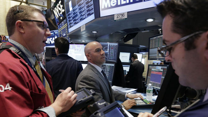 Specialist Henry Becker, center, works with traders at his post on the floor of the New York Stock Exchange Tuesday, March 19, 2013. A surprisingly strong increase in new home construction is sending stocks higher in early trading on Wall Street. (AP Photo/Richard Drew)