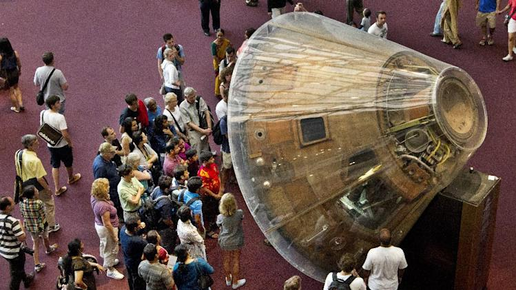 """Visitors gather around the Apollo 11 command module """"Columbia"""" that carried astronauts Neil Armstrong, Buzz Aldrin, and Michael Collins on their historic voyage to the Moon and back on July 16 to 24, 1969, at the Smithsonian Institution's National Aiur and Space Museum in Washington Saturday, Aug. 25, 2012. Neil Armstrong who became a global hero when as a steely-nerved pilot made """"one giant leap for mankind"""" with a small step onto the moon died Saturday. He was 82. (AP Photo/Manuel Balce Ceneta)"""