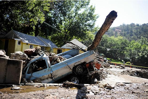 A truck and car is washed away by a flash flood that hit Manitou Springs, Colo., Friday sits in a drainage, covered in rocks, Saturday, Aug. 10, 2013. Friday's torrential rains swept mud, boulders and