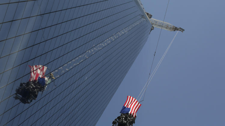 The final piece of spire is hoisted to the roof of One World Trade Center, Thursday, May 2, 2013 in New York.  The piece will be attached to the spire at a later date, capping off the tower at 1,776 feet. (AP Photo/Mark Lennihan)