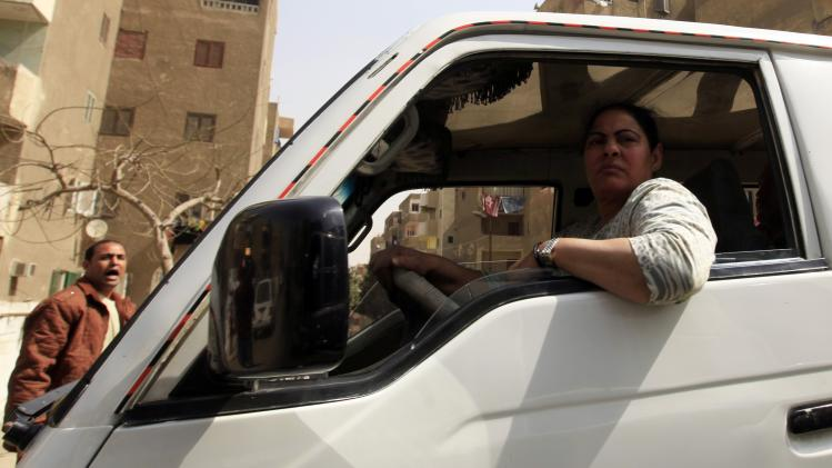 "Nahed, or ""Um Rania"", 52, drives her minibus as a man argues with her in Cairo"