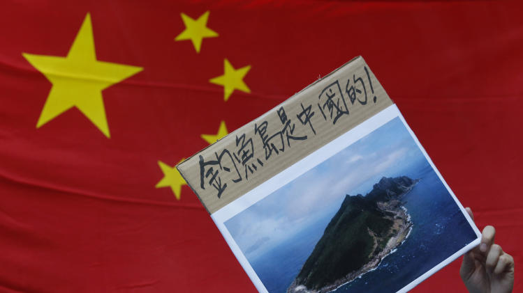 "A protester demonstrating against Japan's claim to disputed islands holds a picture of the rocky islands, known as Senkaku to Japanese and Diaoyu to Chinese, reading ""Diaoyu  belongs to China"" in front of a Chinese national flag during a rally outside the Japanese Consulate General in Hong Kong, Tuesday, Sept. 11, 2012. A territorial flare-up between China and Japan intensified Tuesday as Beijing sent patrol ships near the disputed East China Sea islands in a show of anger over Tokyo's purchase of the largely barren outcroppings from their private owners. (AP Photo/Kin Cheung)"