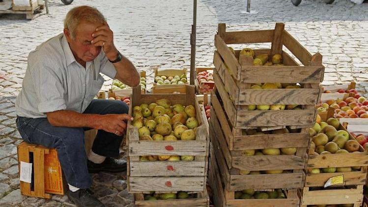 A fruit vendor takes a nap at the Malveira village market on the outskirts of Lisbon