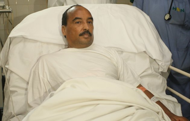 In this Sunday, Oct. 14, 2012, handout photo released by the Mauritanian government news agency AMI (Agence Mauritanienne de l'Information), Mauritanian President Mohamed Ould Abdel Aziz recovers at the Ksar Military Hospital in Noukchott, Mauritania before being evacuated to France for further treatment for a gunshot wound sustained to the arm. Mauritania's Minister of Communication says President Mohamed Ould Abdel Aziz has been lightly wounded by friendly fire after his vehicle was fired upon by the military on the outskirts of the capital, Nouakchott.(AP Photo/Agence Mauritanienne de l'Information)