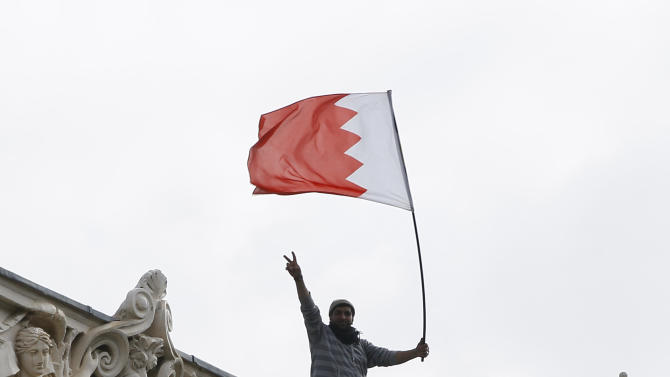 A man waves a flag during a protest from the roof of the Bahrain Embassy  in London,  Monday, April 16, 2012. The banner, draped over the top of the embassy, carried pictures of imprisoned hunger striker Abdulhadi al-Khawaja and senior Shiite opposition leader Hassan Mushaima. Bahrain has been gripped by a 14-month-old uprising aimed at weakening the powers of the kingdom's Sunni monarchy and the Gulf state has recently seen a spike in violence.(AP Photo/Kirsty Wigglesworth)