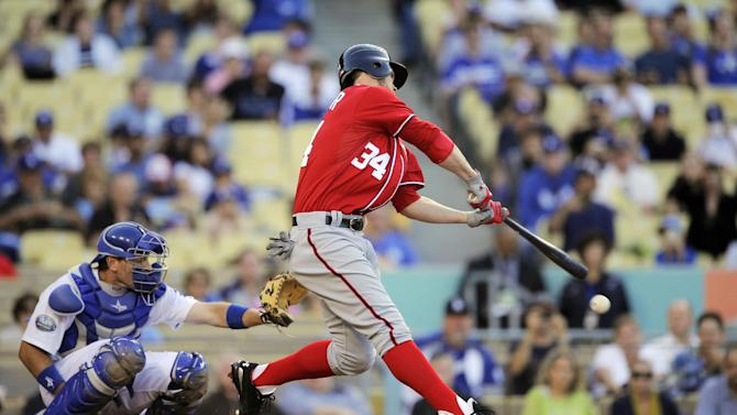 Washington Nationals' Bryce Harper hits as Los Angeles Dodgers catcher A.J. Ellis watches during the second inning of their baseball game, Saturday, April 28, 2012, in Los Angeles. Harper was thrown out at first. (AP Photo/Mark J. Terrill)