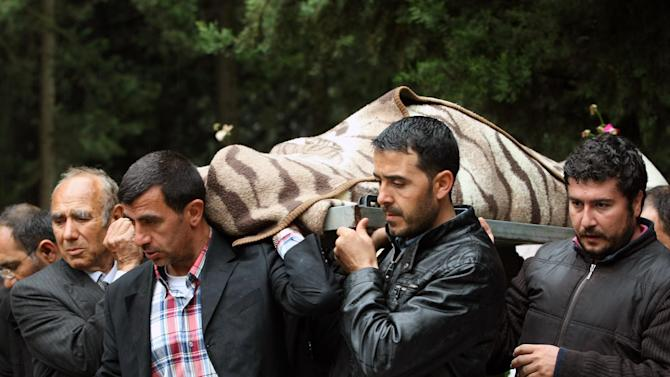 People carry the coffin of Fehmi Karaca, 69, a shop owner and one 46 victims killed in Saturday explosions,  for burial in Reyhanli, near Turkey's border with Syria, Sunday, May 12, 2013.  The bombings marked the biggest incident of cross-border violence since the start of Syria's bloody civil war and have raised fear of Turkey being pulled deeper into the conflict. (AP Photo/Burhan Ozbilici)