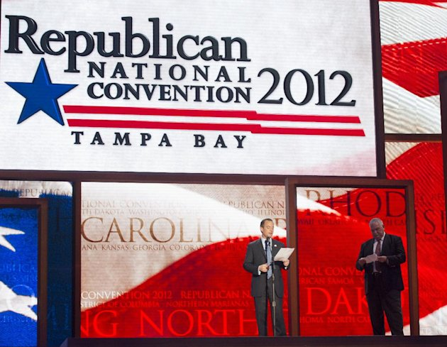 Republican National Committee Chairman Reince Priebus, left, and convention CEO William Harris unveil the stage and podium for the 2012 Republican National Convention, Monday, Aug. 20, 2012, at the Ta