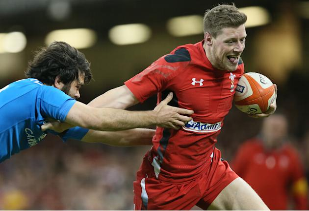 Wales's Rhys Priestland, right, gets away from Italy's Luke McLean during their Six Nations international rugby union match between Wales and Italy at the Millennium stadium in Cardiff, Wales,