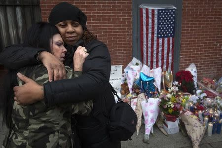 Donna Salvaggio and a woman who gave her name as Reverend Jordan hug at a makeshift memorial at the site where two police officers were shot in the head in the Brooklyn borough of New York