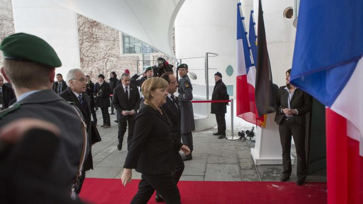 German Chancellor Angela Merkel, front, accompanies French President Francois Hollande, background, into the Chancellery in Berlin, Germany, Tuesday, Jan. 22, 2013. France and Germany mark 50 years since they signed the Elysee Treaty, the post-war friendship pact between the former enemies. (AP Photo/Gero Breloer)