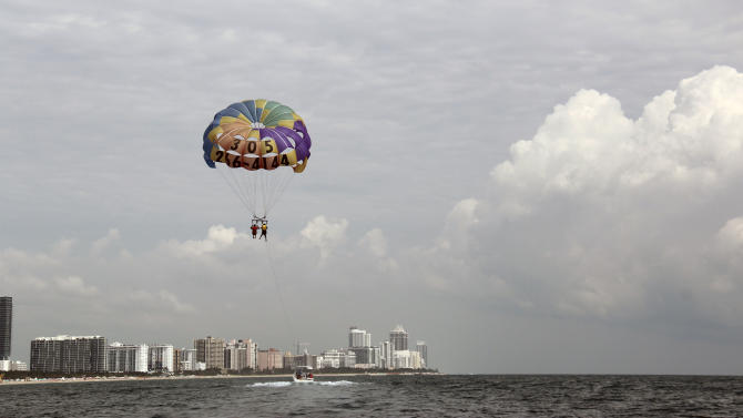 In this Sept. 24, 2012 photo, two people parasail over Miami Beach, Fla.  Soaring high above the ocean off South Beach, tethered only by a rope to a boat hundreds of feet below, riding in a parasail is at once exhilarating and oddly peaceful, even quiet. For millions of people, that's the takeaway from a once-in-a-lifetime experience. But every year there are accidents, some of them fatal. The Parasail Safety Council, which tracks injuries and deaths from the activity nationwide, reports more than 70 people have been killed and at least 1,600 injured between 1982 and 2012, out of an estimated 150 million parasail rides during those 30 years. Despite the inherent risk, few federal or state safety regulations exist for parasailing. In Florida, which has by far the largest number of parasail operators at about 120, repeated efforts to enact new rules following fatal accidents have landed with a thud. Florida is seen by safety proponents as a national bellwether because of parasailing's popularity in the state. (AP Photo/Tony Winton)
