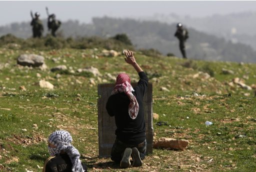 Palestinian protester gestures in front of Israeli border police during clashes at a weekly protest against Jewish settlements near Ramallah
