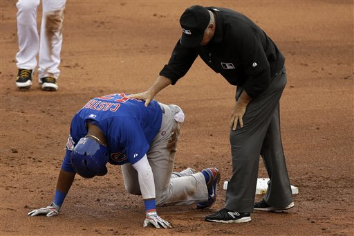 Chicago Cubs' Starlin Castro (13) is checked by second base umpire Tim Timmons while getting up slowly after being tagged out attempting to stretch a single into a double during the sixth inning of a