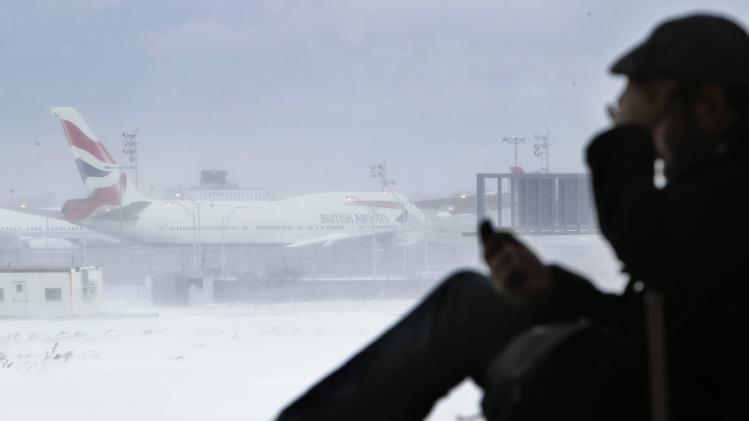 Kevin Fagan, from San Francisco, talks on his phone while an airplane sits motionless on the runway at John F. Kennedy International Airport in New York, Monday, Dec. 27, 2010. Fagan was trying to get to Berlin, Germany when the blizzard hit and was forced to sleep in the airport. (AP Photo/Seth Wenig)