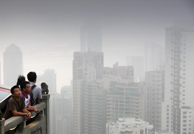 People look across the Hong Kong skyline shrouded by smog.
